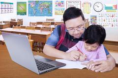 Stock Photo of Teacher teach his student to write