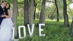Young beautiful couple, bride and groom in the park, with the word love, hugging Stock Footage