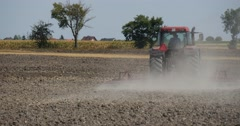Tractor Distantly is Moving to the Left Tractor is Plowing The Field Road along Stock Footage