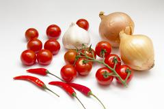 An arrangement of onons, tomatoes, chillies and garlic on a white background Stock Photos