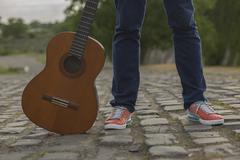 Man's legs in jeans with guitar empty country road Kuvituskuvat
