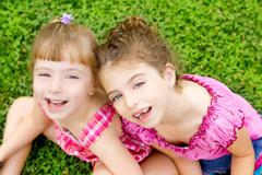 Children girls laughing sit on green grass Kuvituskuvat