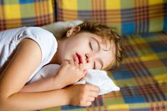 child girl sleeping bed in retro vintage quilt - stock photo