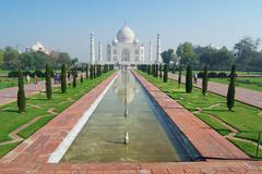 People explore Taj Mahal mausoleum at sunrise in Agra, India. Stock Photos