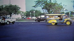 MANILA, PHILIPPINES 1973: Classic Jeepney driving past busy urban intersection. Stock Footage