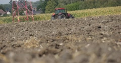 Tractor is Plowing The Soil of Field Soil Close Up Tractor is Far from Camera Stock Footage