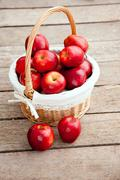 Stock Photo of basket of red apples on wood floor