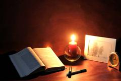 Meditations, exposed book and burning candle Stock Photos