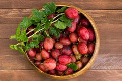 Red gooseberries in a wooden bowl - stock photo
