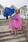 Holidaymaker with an umbrella and poncho at the seaside on a wet day - stock photo
