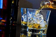Barman pouring whiskey in two glasses with ice cubes on table with light tint Stock Photos