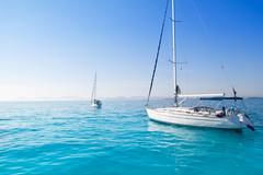 Anchored sailboats in turquoise Formentera beach Stock Photos