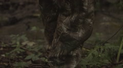 Follow shot of a hunter walking through puddles in the woods Stock Footage
