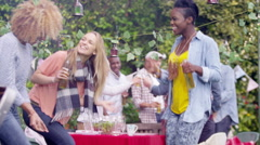 4K Happy mixed ethnicity group of dancing & drinking beer at bbq party - stock footage