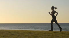 Sporty Girl Jogging in the park sunrise / sunset slow motion Stock Footage