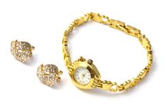 Golden wrist watch and earrings Stock Photos