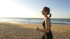 Girl running outdoors jogging to increase fitness through exercise slow motion Stock Footage