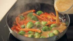 Stock Video Footage of Omelette with Red Paprika, Brussel Sprouts and Onions Frying on a Pan