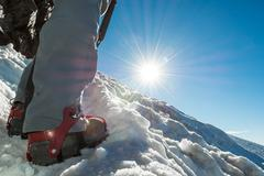 Close up of hiking shoes with crampons and ice axe. - stock photo