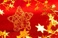 christmas gold wire star on red glitter - stock photo