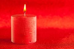 Christmas candle candlelight on red glitter Stock Photos