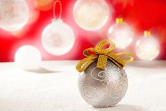 Christmas silver bauble with golden loop on snow Stock Photos