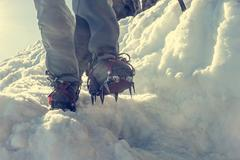 Close up of hiking shoes with crampons and ice axe. Stock Photos