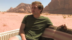 Man Riding in the Back of a Truck through the Wadi Rum, Jordan Stock Footage