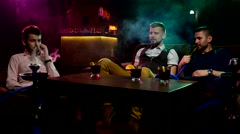 Boys smoking hookah in the caffee Stock Footage