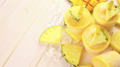 Homemade low calorie popsicles made with mango, pineapple and coconut milk. Stock Footage