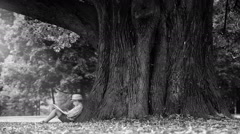 Black and white footage: a boy reading book under enormously big linden tree Stock Footage