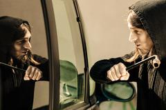 Transportation and crime- thief breaking car window Stock Photos