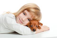blond kid girl with mini pinscher pet mascot dog - stock photo