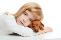 Blond kid girl with mini pinscher pet mascot dog Stock Photos