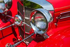 Red detail on the headlight of a vintage beautiful car - stock photo