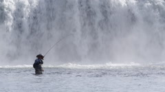 Man Catches Fish with Wall of Water behind Stock Footage