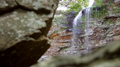 Waterfall Behind Huge Bolders Summertime Stock Footage