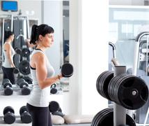 Woman with weight training equipment on sport gym Stock Photos