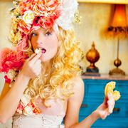 Stock Photo of baroque fashion blonde woman eating dona
