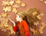 Autumn girl on dried leaves blowing wind lips Stock Photos