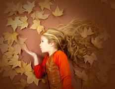 autumn girl on dried leaves blowing wind lips - stock photo