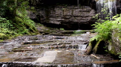 Water cascades over mossy rocks Stock Footage