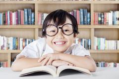 Stock Photo of Child showing a toothy smile in the library