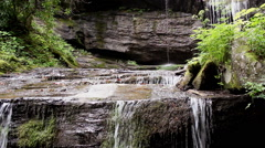 Water cascades over mountain rocks Stock Footage