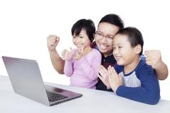 Joyful kids clapping hands with father Stock Photos