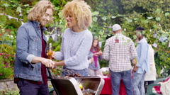 4K Happy attractive couple cooking at bbq while friends socialize in the backgro - stock footage