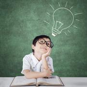 Primary school student imagining a light bulb - stock photo