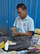 Stock Photo of A street bookseller in Yangon, Myanmar (Burma) repairs a paperback while mind