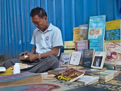 Medium close up of a street bookseller in Yangon, Myanmar (Burma) repairs a p Stock Photos