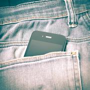 smart phone in jean pocket retro vintage style - stock photo